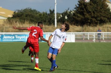 Harrow's Lewis Ochoa (L) heads clear from Harry Ottaway
