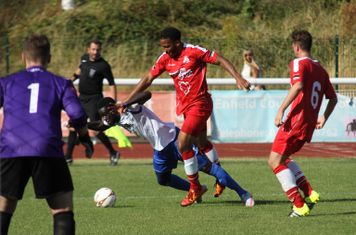 Enfield's Kelvin Bossman goes down under a challenge from Shaun Preddie