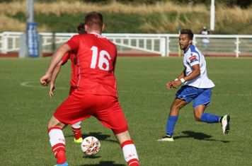 Enfield's Tyler Campbell plays the ball between Michael Peacock and (?) David Taylor