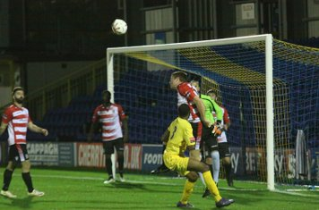 Kingstonian's George Wells heads clear from Ricky Gabriel (yellow)
