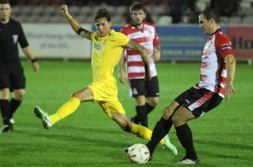 Enfield's Tom Collins (L) tries to close down Bruce Hogg's clearance