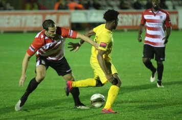 Enfield's Dernell Wynter (yellow) takes the ball past Bruce Hogg