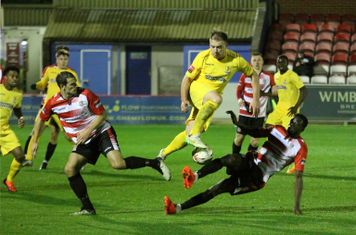 Enfield's Jordan Lockie (yellow) tries to take the ball between Bruce Hogg (L) and Michael Onovwigun