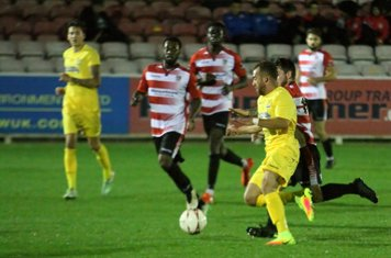 Enfield's Nigel Neita (yellow) is nudged off the ball by Aaron Lamont