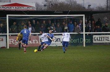 Enfield's Harry Ottaway (white, L) holds off Sam Nunn
