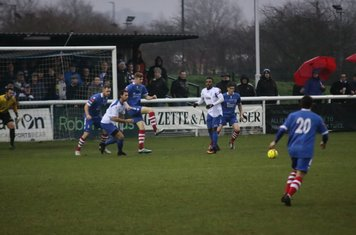 Needham's Billy Holland (blue, centre) clearsm but only as far as Billy Crook who returned the ball into the top corner.