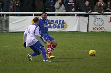Needham's Luke Ingram (blue) clears from Billy Crook