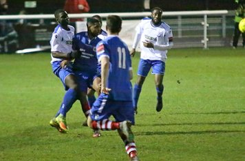 Enfield's Percy Kiangebeni (L) clears from Reece Dobson
