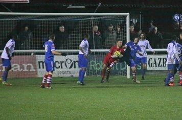 Needham's Sam Nunn challenges Enfield keeper Nathan McDonald