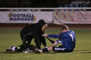 Hendon keeper Tom Lovelock receives treatment for an early injury.