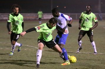Hendon's Jamie Smith (green) tackles Percy Kiangebeni