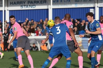 Enfield's Taylor McKenzie (L) hits Paul Konchesky (3) with his header