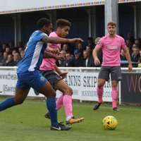 Billericay's Leo Chambers (blue) challenges Montell Moore