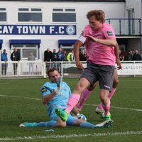 After saving Simon Thomas's penalty, Billericay keeper Alan Julian gets to the rebound ahead of Thomas and Aaron Greene