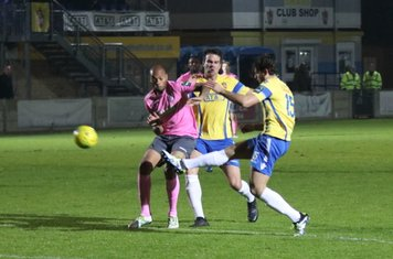 Staines' Greg Haydon (R) clears from Simon Thomas