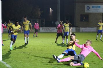 Enfield's Ryan Blackman (R) and Staines' Lewis Driver slide in but can't make contact