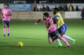Staines' Tyrell Miller-Rodney (R) nudges Drew Roberts in the back to concede a free kick