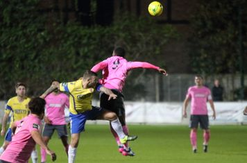 Staines' Tommy Brewer (yellow) challenges Ryan Blake