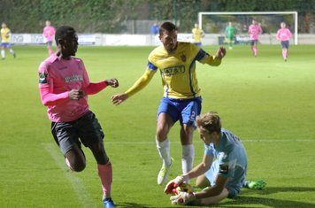 Staines' keeper Liam Driscoll collects the ball ahead of Ryan Blake (L) and Josh Webb