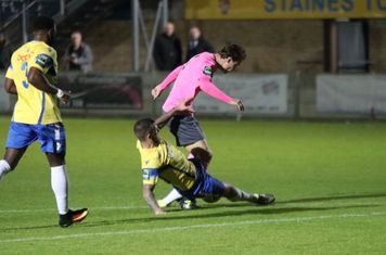 Staines' Tommy Brewer (yellow) tackles Mickey Parcell