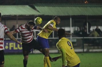 Kingstonian's Kevin MacLaren (hoops) heads clear from Simon Thomas