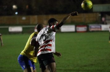 Kingstonian's Leo Chambers (R) heads clear from Simon Thomas