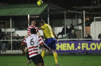 Enfield's Mark Kirby (yellow) challenges Manolis Gogonas