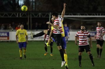 Kingstonian's Sean Francis (hoops) heads clear from Simon Thomas