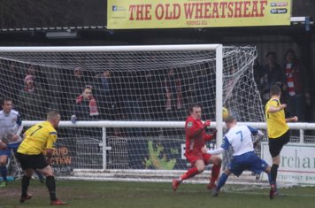Kingstonian's Greg Cundle (R) hits the side netting under the challenge of Ryan Blackman