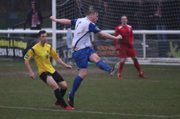 Enfield's Mark Kirby clears from Greg Cundle