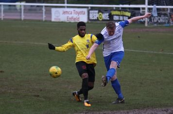 Enfield's Mark Kirby (R) clears from Andre McCollin