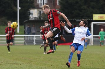 Brightlingsea's Jake Gould heads clear from Tyler Campbell (R)