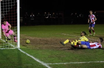 After the ball had rebounded off the far post, Dorking keeper Slavomir Huk gets across to block Dernell Wynter's follow up