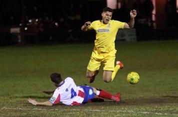 Dorking's Dean Hamlin (4) earens a yellow card with a challenge on Samir Bihmoutine
