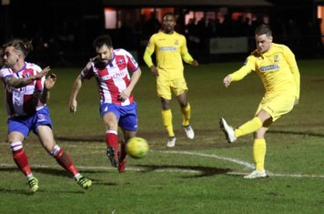 Enfield's Liam Hope shoots as Jerry O'Sullivan (L) and Dean Hamlin try to block
