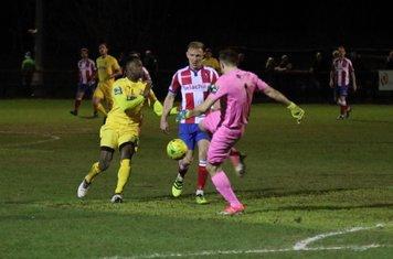 Dorking keeper Slavomir Huk clears from Ryan Blake