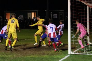 Enfield's Liam Hope (yellow, R) tries to backheel the ball towards goal but is crowded out by the defence