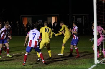 Enfield's Liam Hope (yellow, R) brings the ball down in the goalmouth