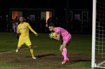 Dorking keeper Slavomir Huk reaches the ball ahead of Liam Hope