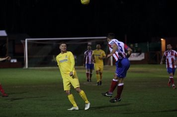 Dorking's David Ray (R) heads clear from Liam Hope
