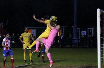 Dorking keeper Slavomir Huk catches under pressure from Matt Johnson