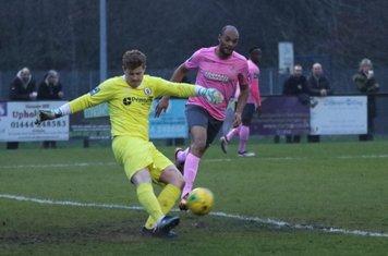 Burgess Hill keeper Josh James clears from Simon Thomas