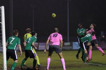 Enfield's Dan Rumens (pink, R) heads over the bar