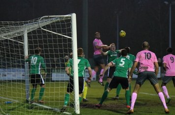 Enfield's Mat Mitchel-King (pink, L) heads the ball across the box