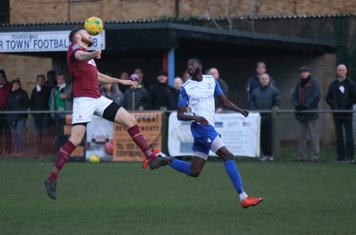 Potters Bar's James Budden (L) heads clear from Muhammadu Faal