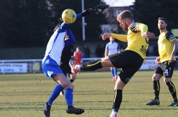 Enfield's Sam Youngs (L) tries to block a clearance from Ben Swift