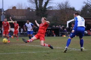 Hornchurch's George Winn (red, R) tries to block a shot from Billy Bricknell (R)
