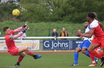 Enfield's Kezie Ibe (white) lifts the ball over keeper Zaki Oualah but over the bar