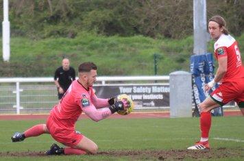 Leatherhead keeper Zaki Oualah saves Dan Rumens's header as Will Salmon covers any fumble