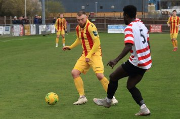 Kingstonian's Ismail Yakubu (R) clears from Billy Bricknell